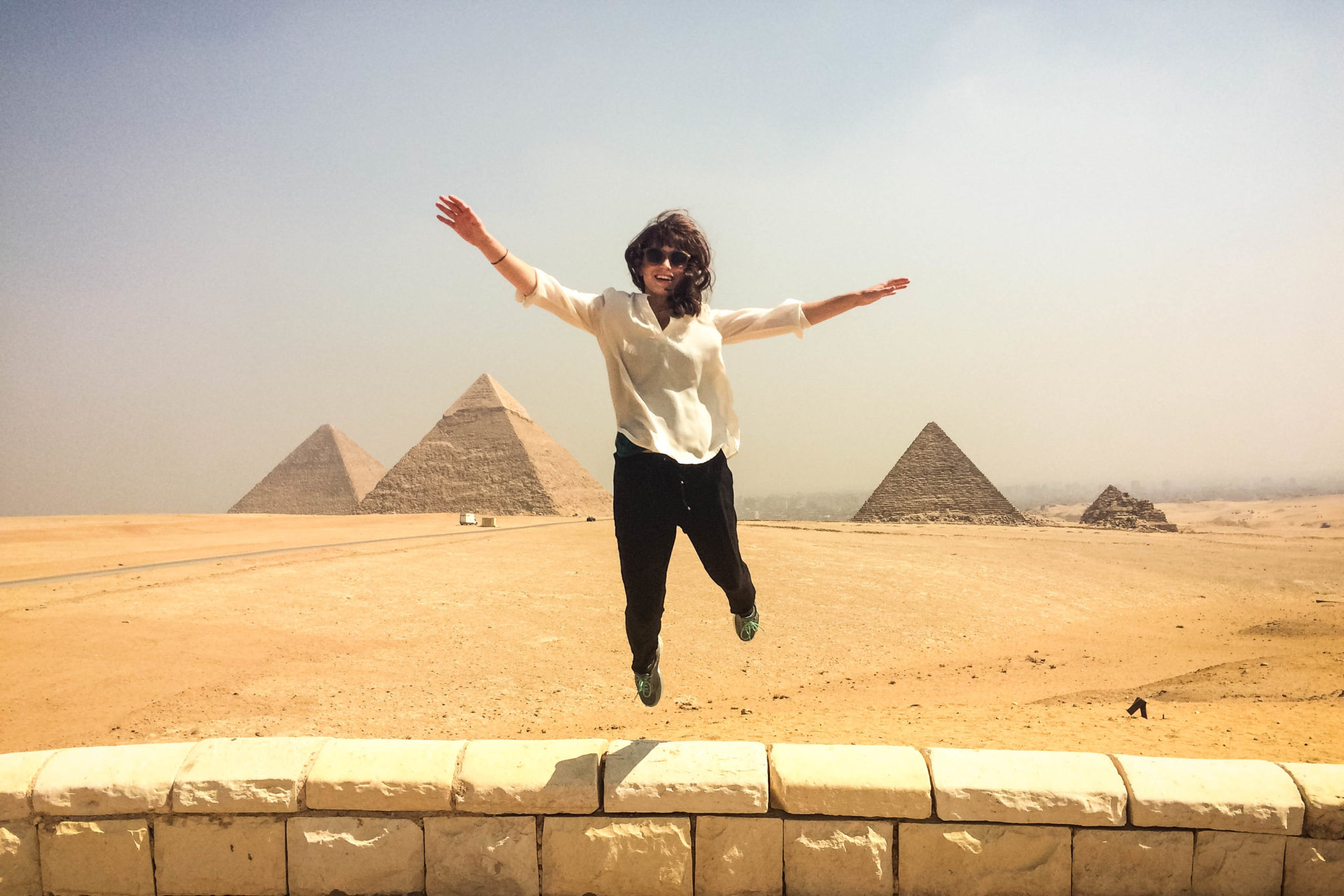 Jumping in front of the Pyramids of Giza in Egypt